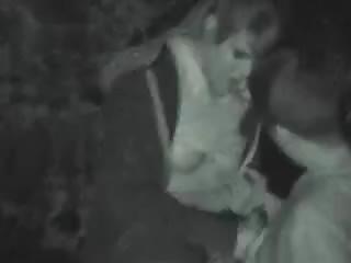 Jeune couple fait l'amour en pleine nuit dans un parc