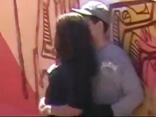 Jeune couple pris en flag en train de baiser dans une ruelle