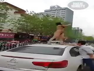 Une folle à poil sur le toit d'une voiture